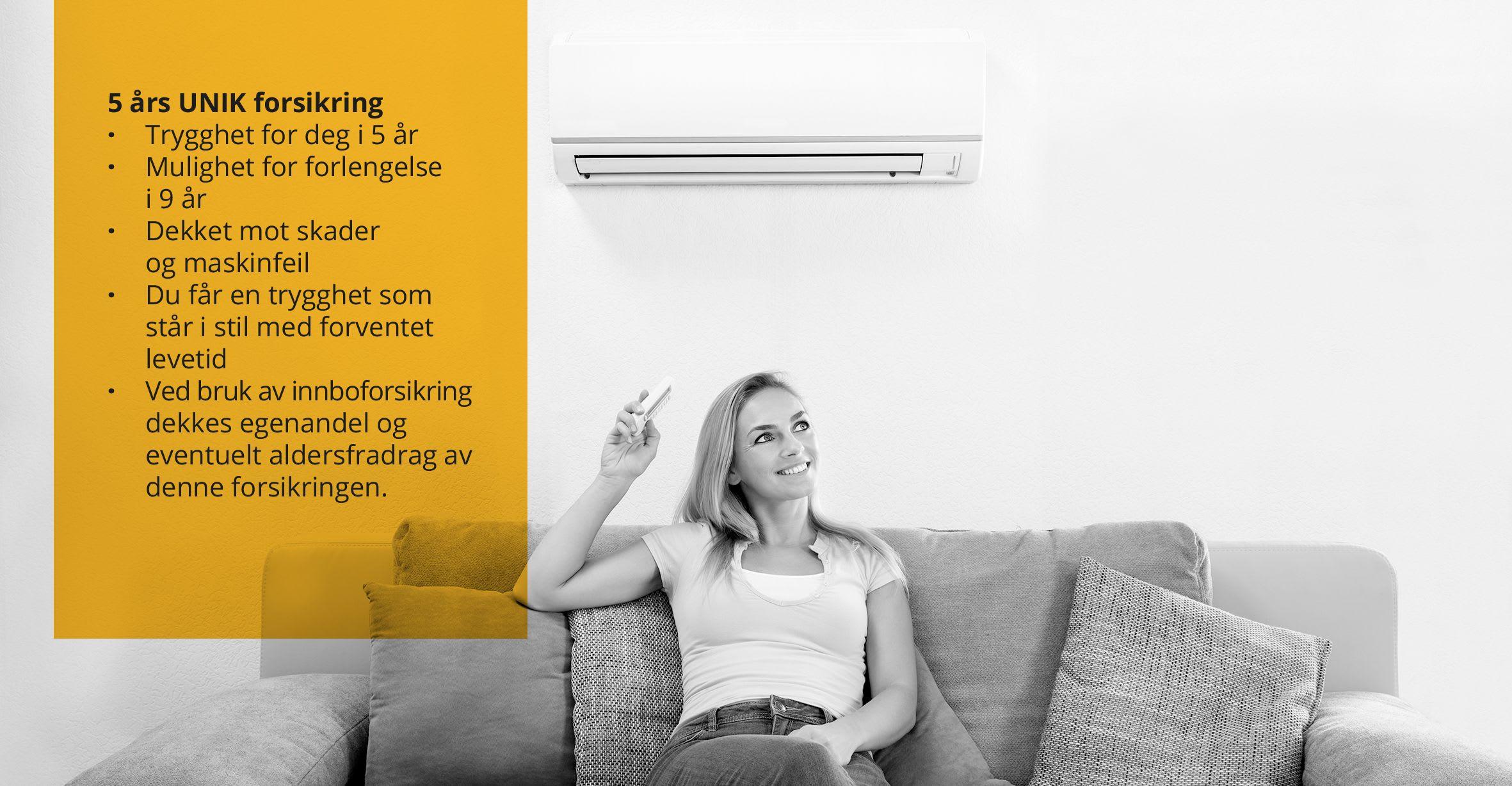 En ung dame sitter i sofa med en varmepumpe hengt på veggen.