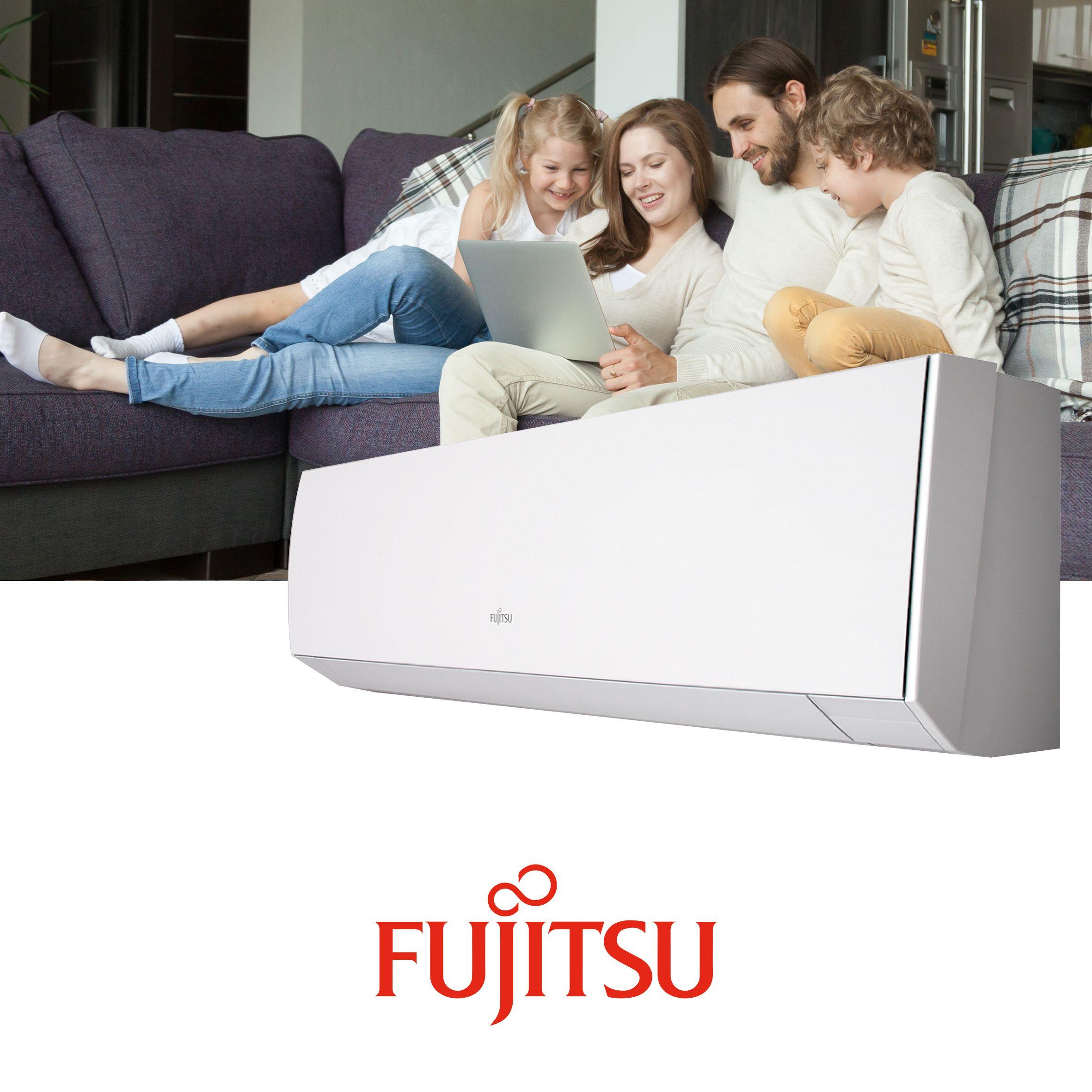 Familie på fire med mor, far, datter og sønn sitter i en sofa og ser på en PC, i en stue med Fujitsu varmepumpe.