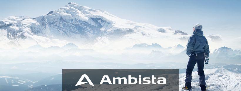 Mann står på toppen av et fjell og ser utover et vinterlandskap.