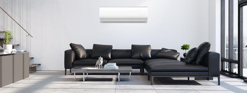 Stue med en hvit Midea varmepumpe hengt på veggen over sofaen.