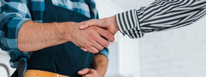 En forhandler og leverandør som inngår en avtale og tar hverandre i hendene.