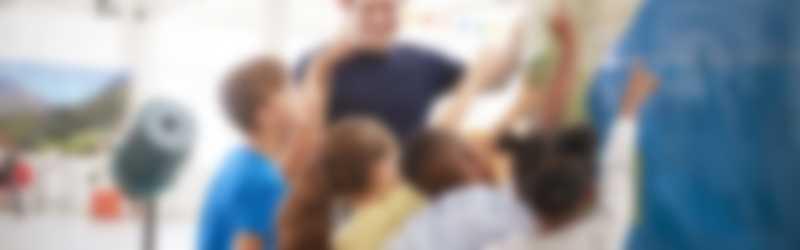 Meester met kinderen wijzend naar wereldbol