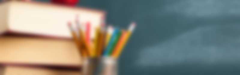 schoolbord met stapel boeken en appel