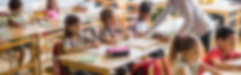 Oudere leerkracht in een klas vol kinderen