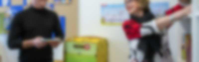 Iemand geeft boekjes aan een lerares die de boekjes in de kast plaatst