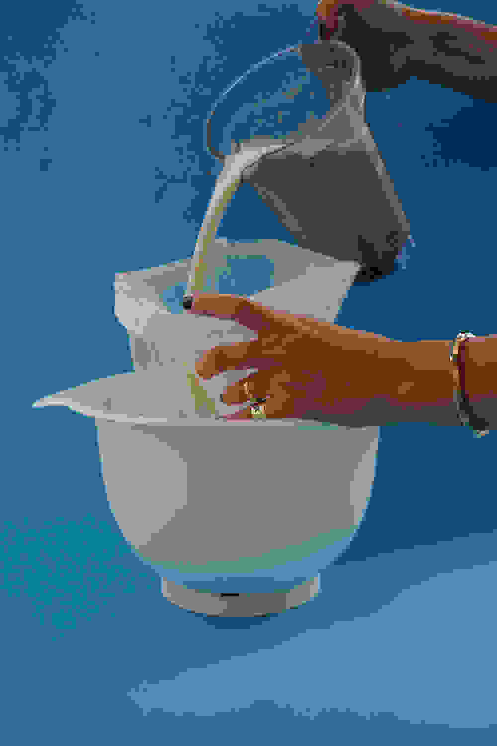 pouring almond milk into a nut milk bag