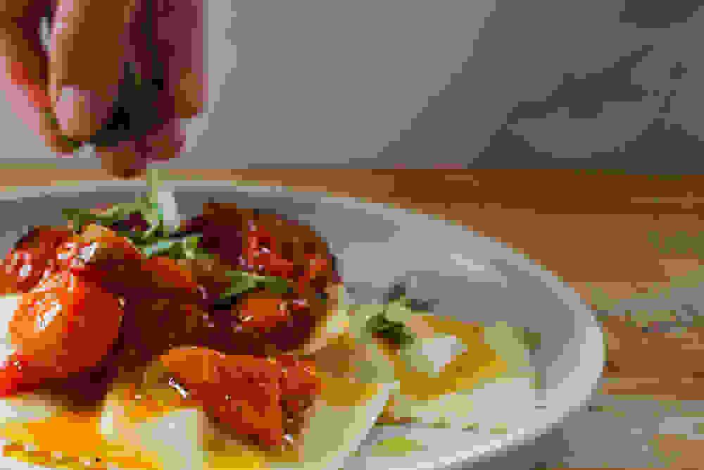 garnishing the ravioli and cherry tomato sauce with fresh oregano