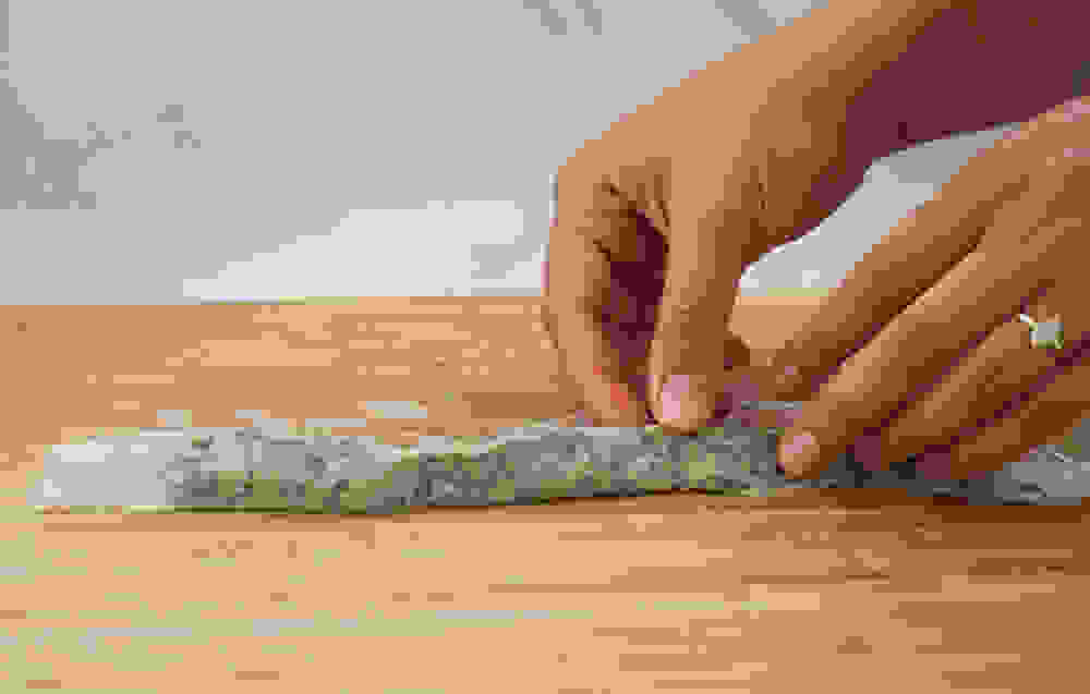 rolling the rice paper into a tight long sausage-shaped roll