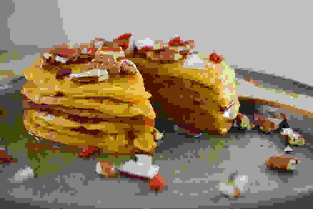tall pancakes stack with pecans coconut goji berries and maple syrup on top