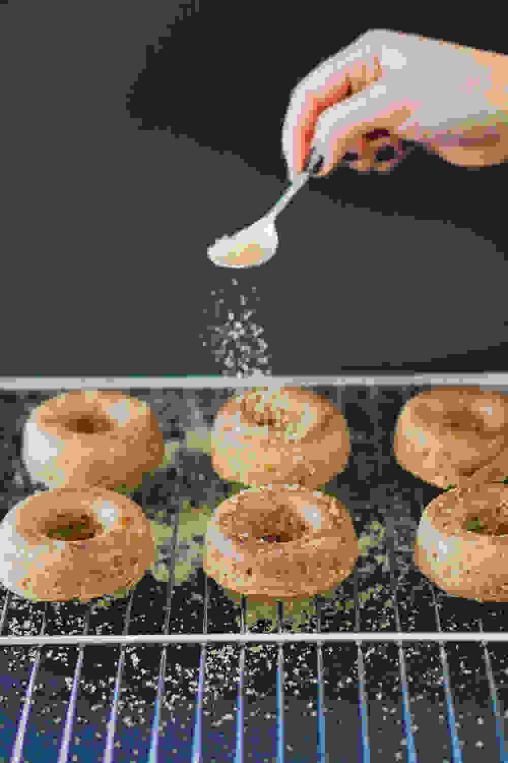 sprinkling cinnamon-sugar on the baked doughnuts