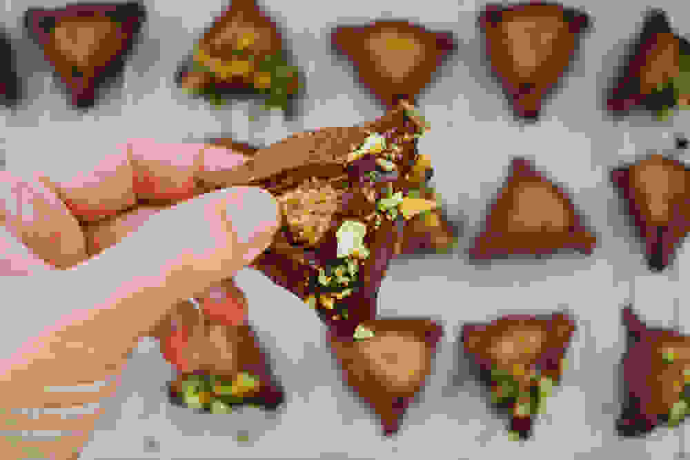 holding a chocolate hamantaschen with pistachio filling and chocolate cover