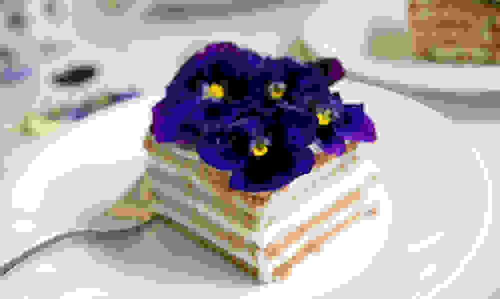 a piece of no bake vegan cheese cake with purple flowers