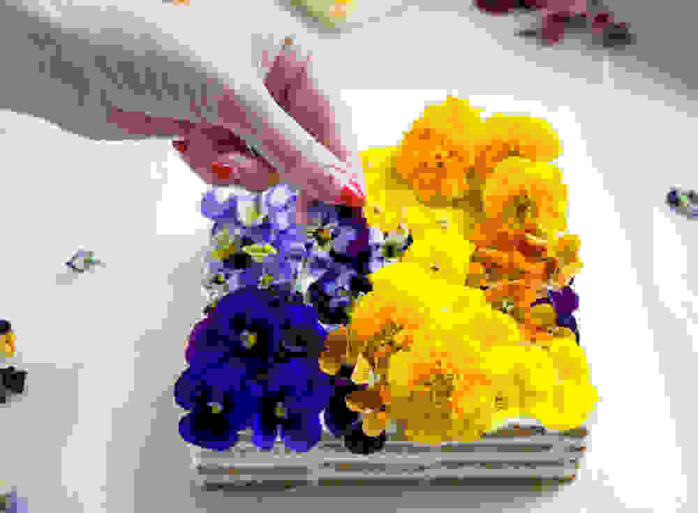 Bini decorating the cake with edible flowers