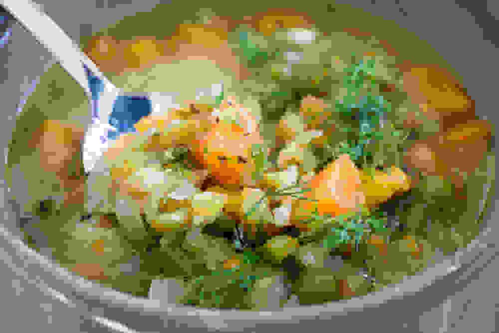 כף של מרק אפונה יבשה טבעוני עם שמיר ירקות כתומים ולימון