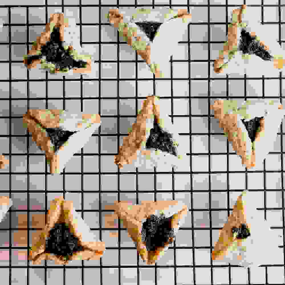 baked hamantaschen with poppy seed on a wire rack