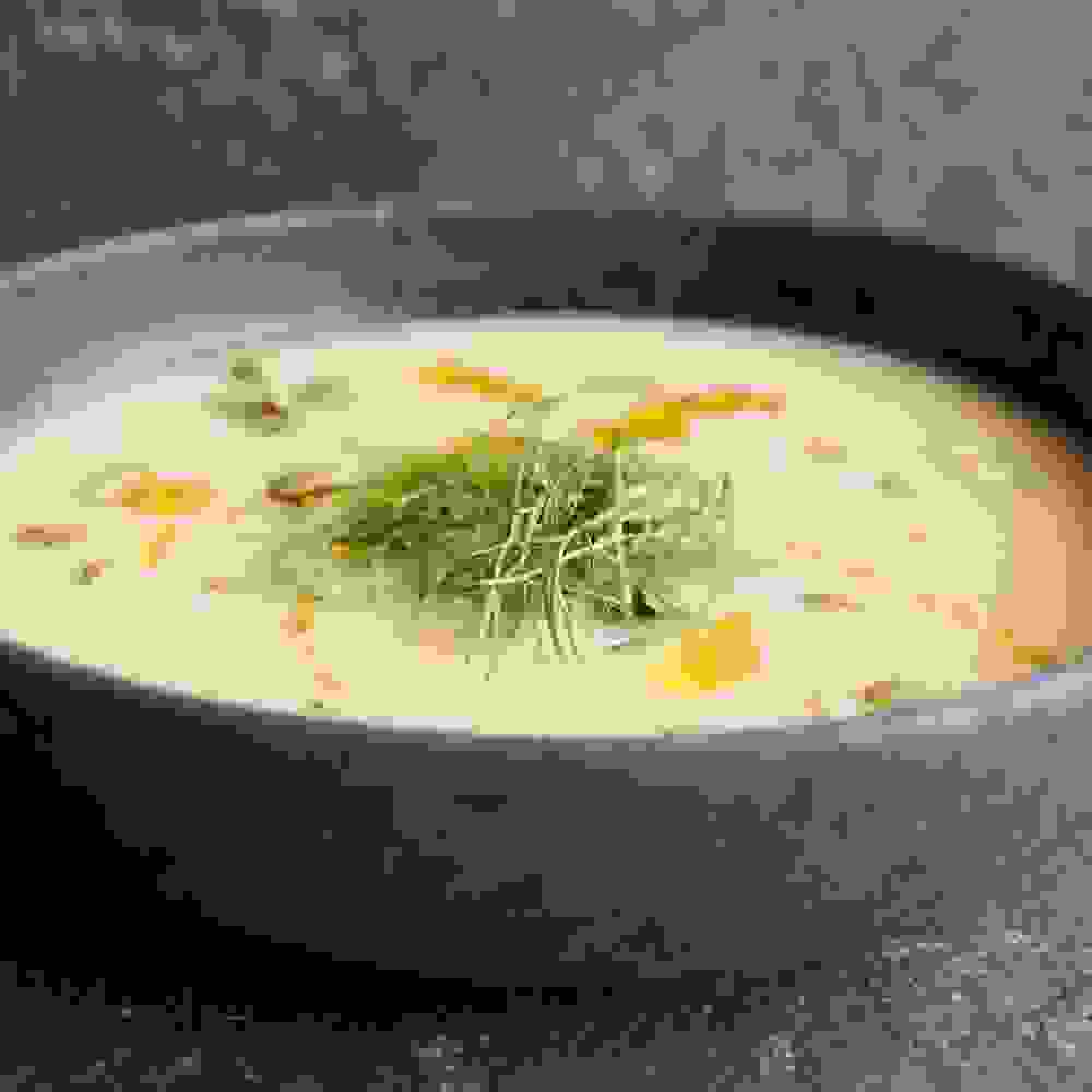 creamy white root vegetable soup with dill and pumpkin seeds