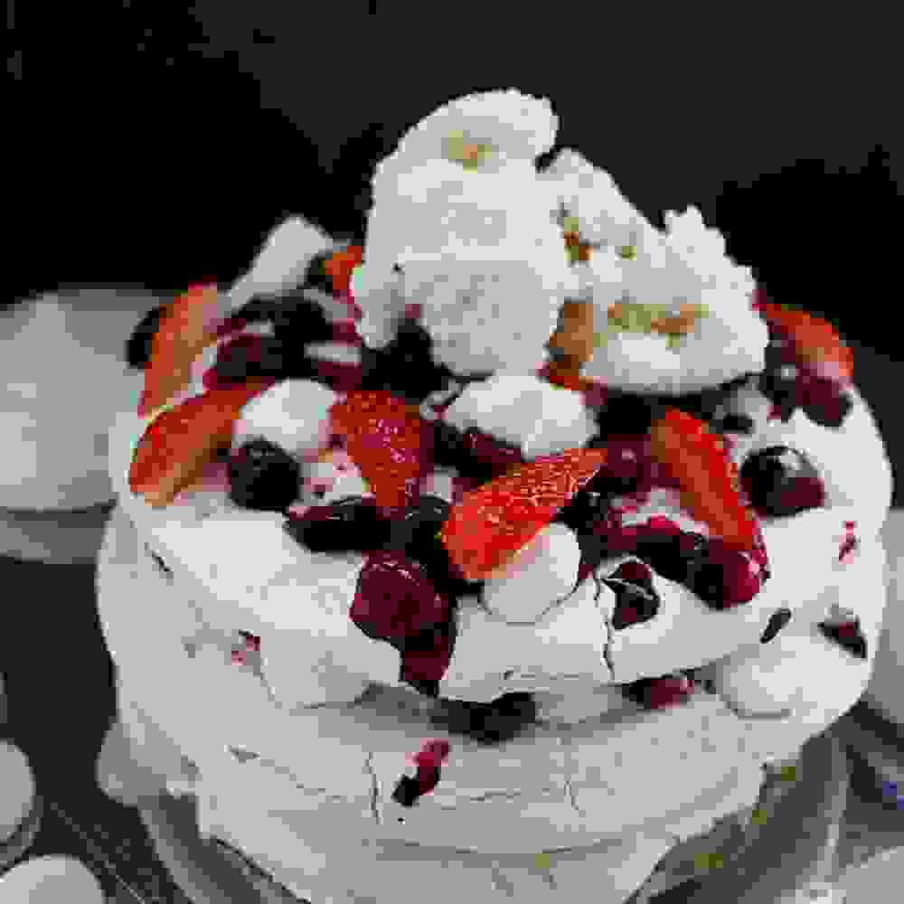 vegan pavlova cake with coconut ice cream whipped cream and berry compote