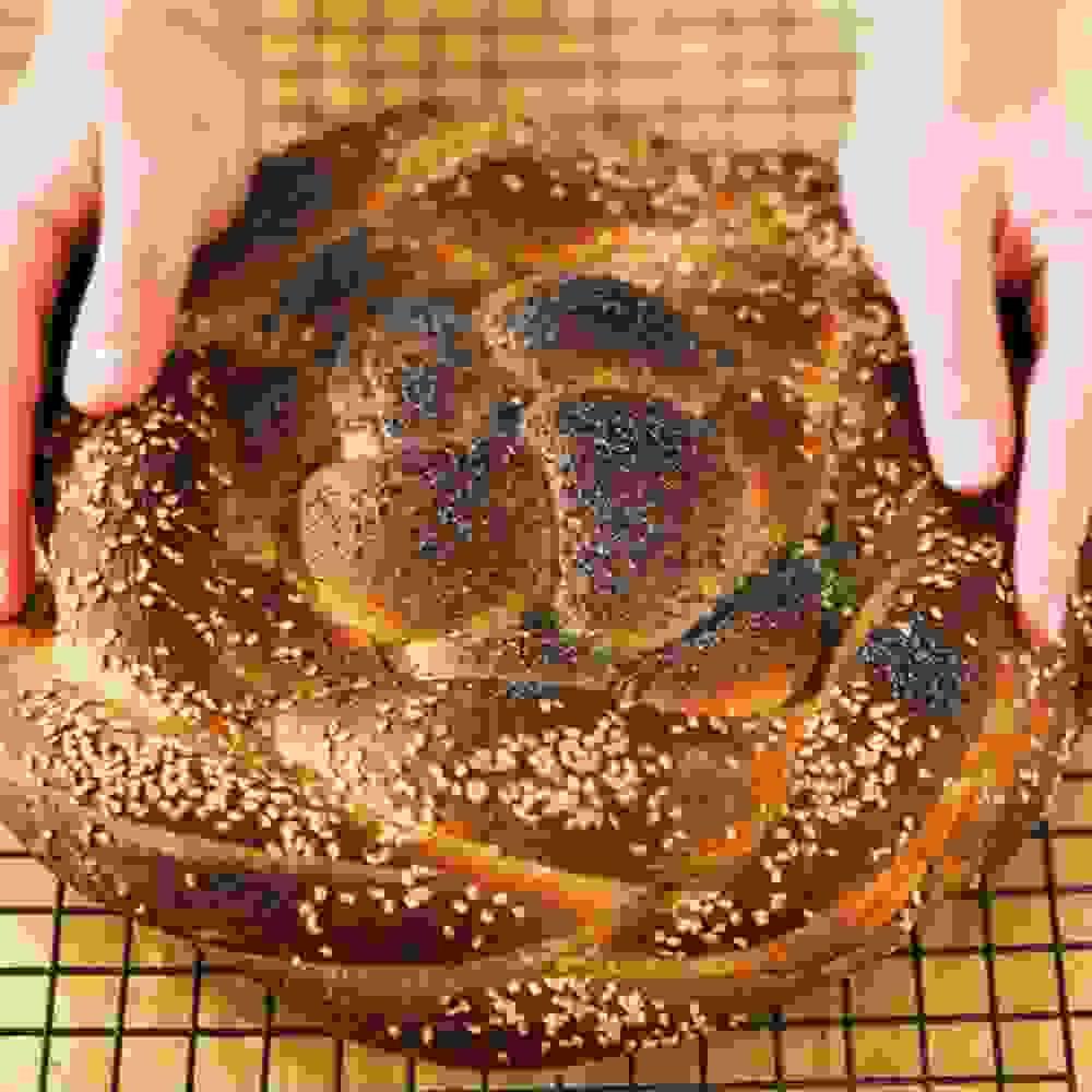 hands holding baked vegan spelt challah