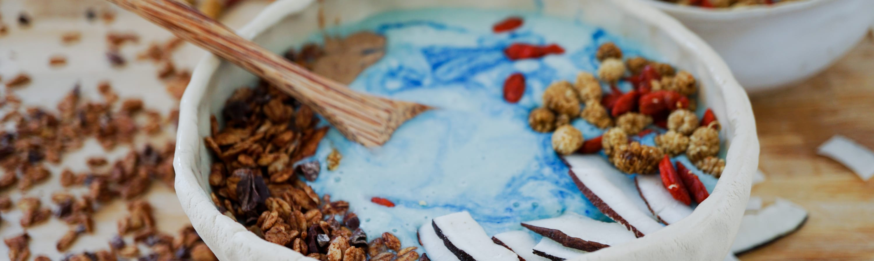 blue majik spirulina smoothie bowl with toppings and a wooden spoon