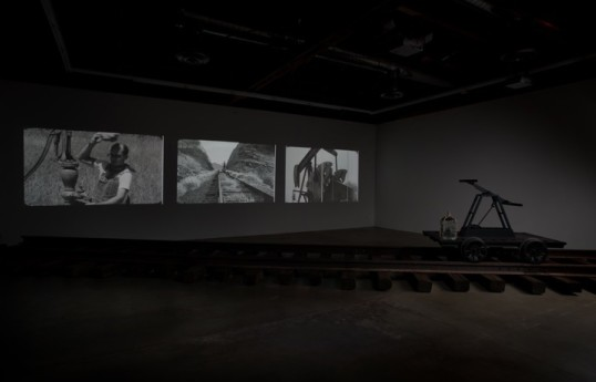 Pumping, 2010, Three channel Blue-ray video installation, custom steel handcar, water jug, railroad tracks, film strips/pile of metal, Dimensions variable, Installation View