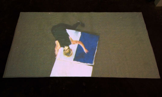 "Continual Maintenance and Mending, 2007, Single channel video, 54:49 minutes looped, Projection size 60"" x 107"", projected onto a white handmade quilt"
