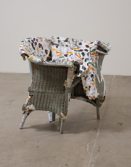 "Hogtie, 2011, Wicker loveseat, paper mache of high interest loan papers and Martha Stewart magazine images, 39"" x 42"" x 33"""