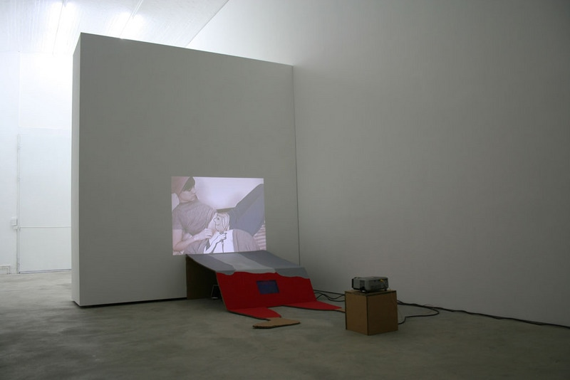 "Peas, 2007, Video Installation with 2 DVD players, video/audio projector, video monitor, cardboard figure, 92"" x 59"""