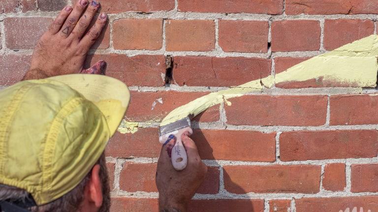 Peinture jaune sur mur de brique