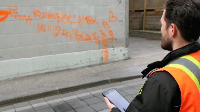 Un inspecteur regarde un graffiti orange sur le mur