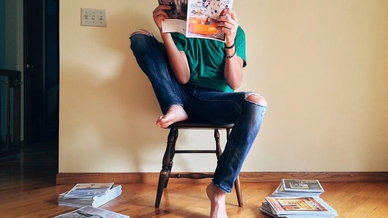 Adolescent en train de lire sur une chaise.