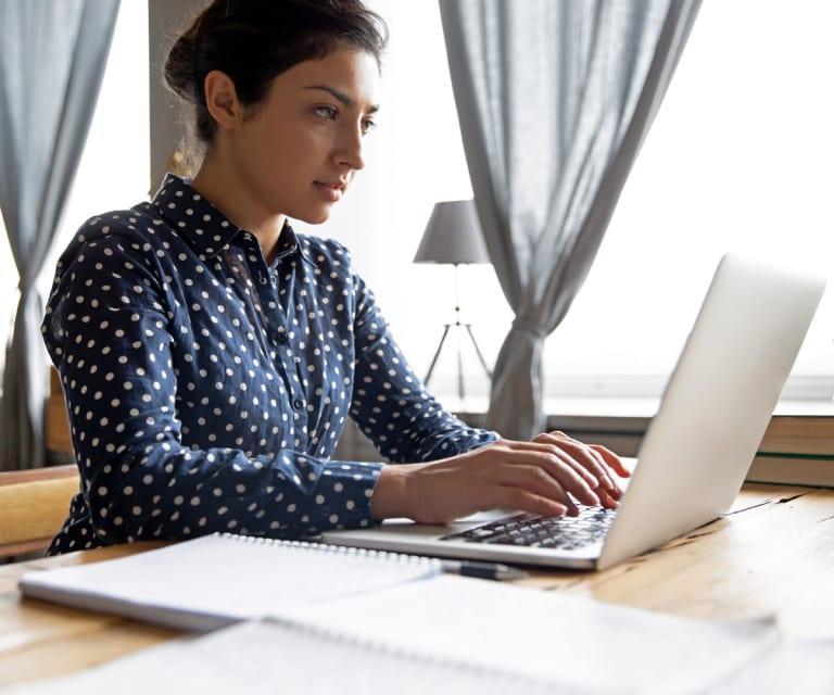 Une femme dans un cadre professionnel utilise son ordinateur