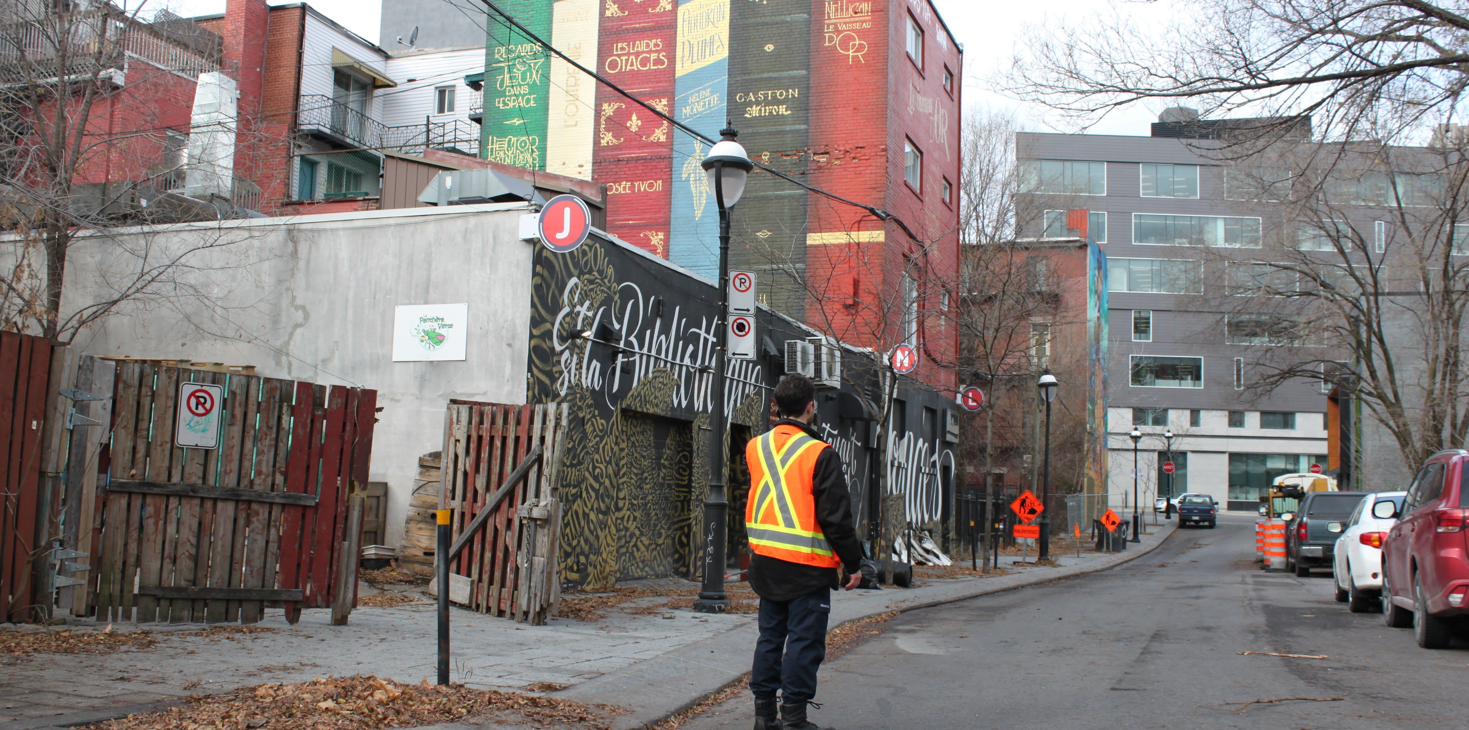 Un homme de dos dans une ruelle avec des graffitis