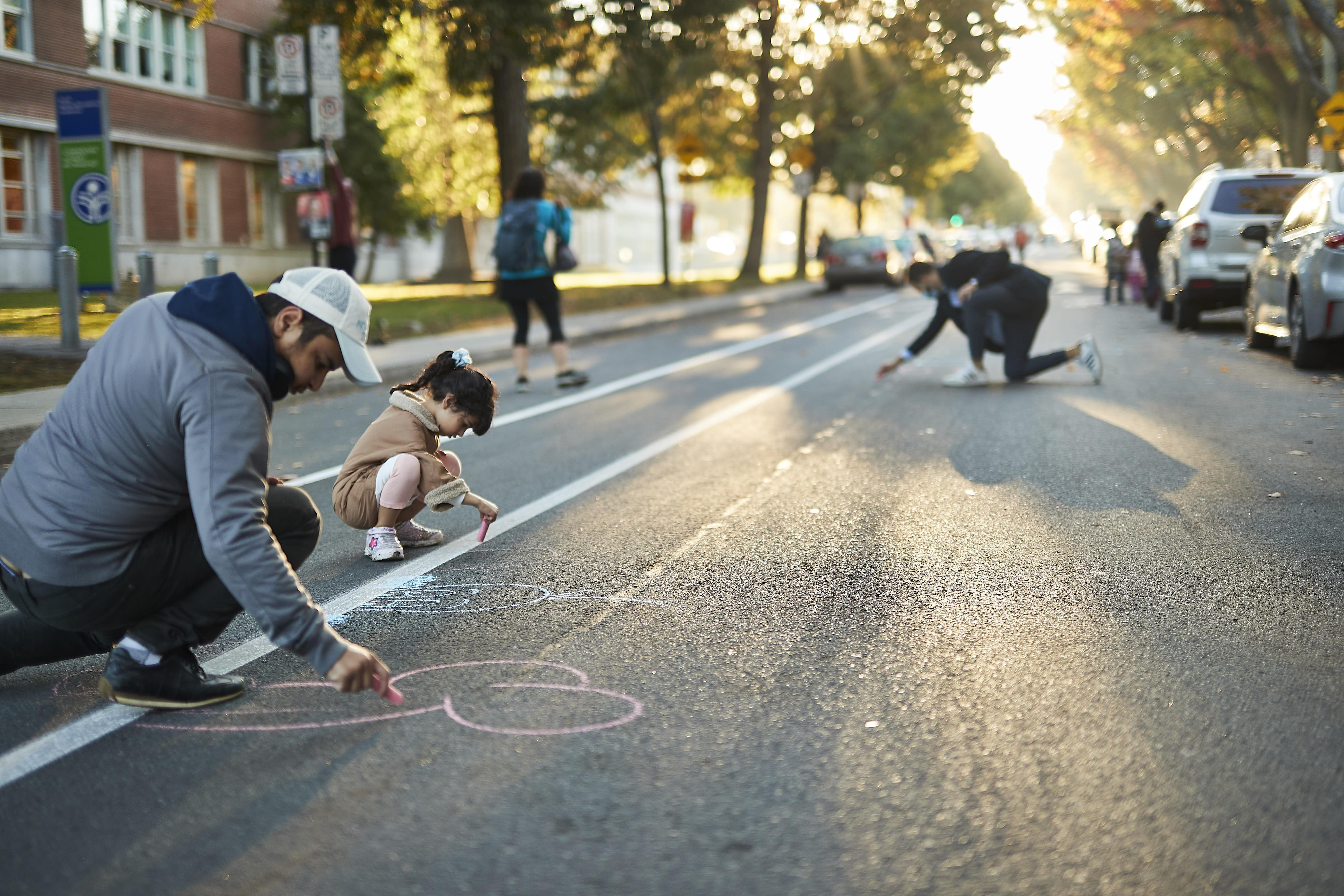 Un papa et sa fille dessinent dans la rue-école