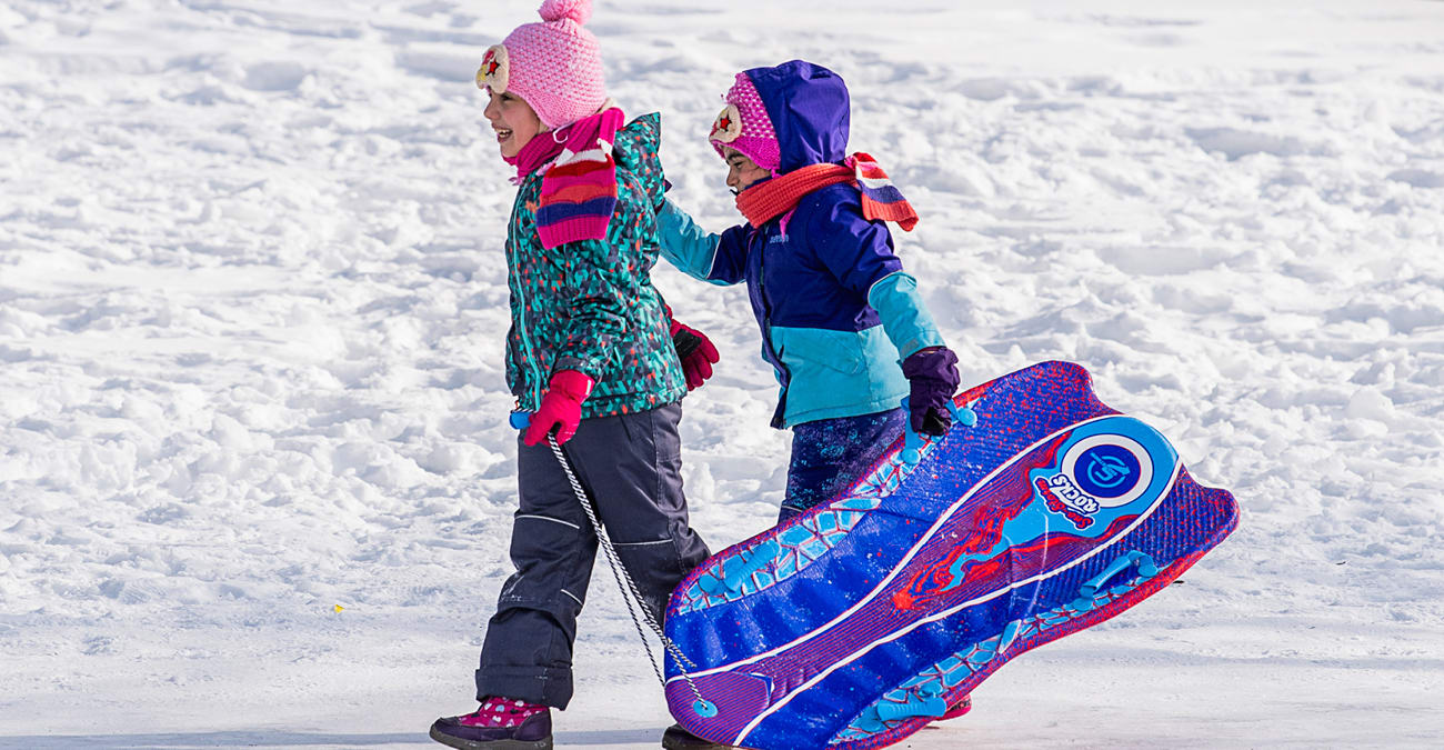 Two girls carry their sled on a sunny winter day.