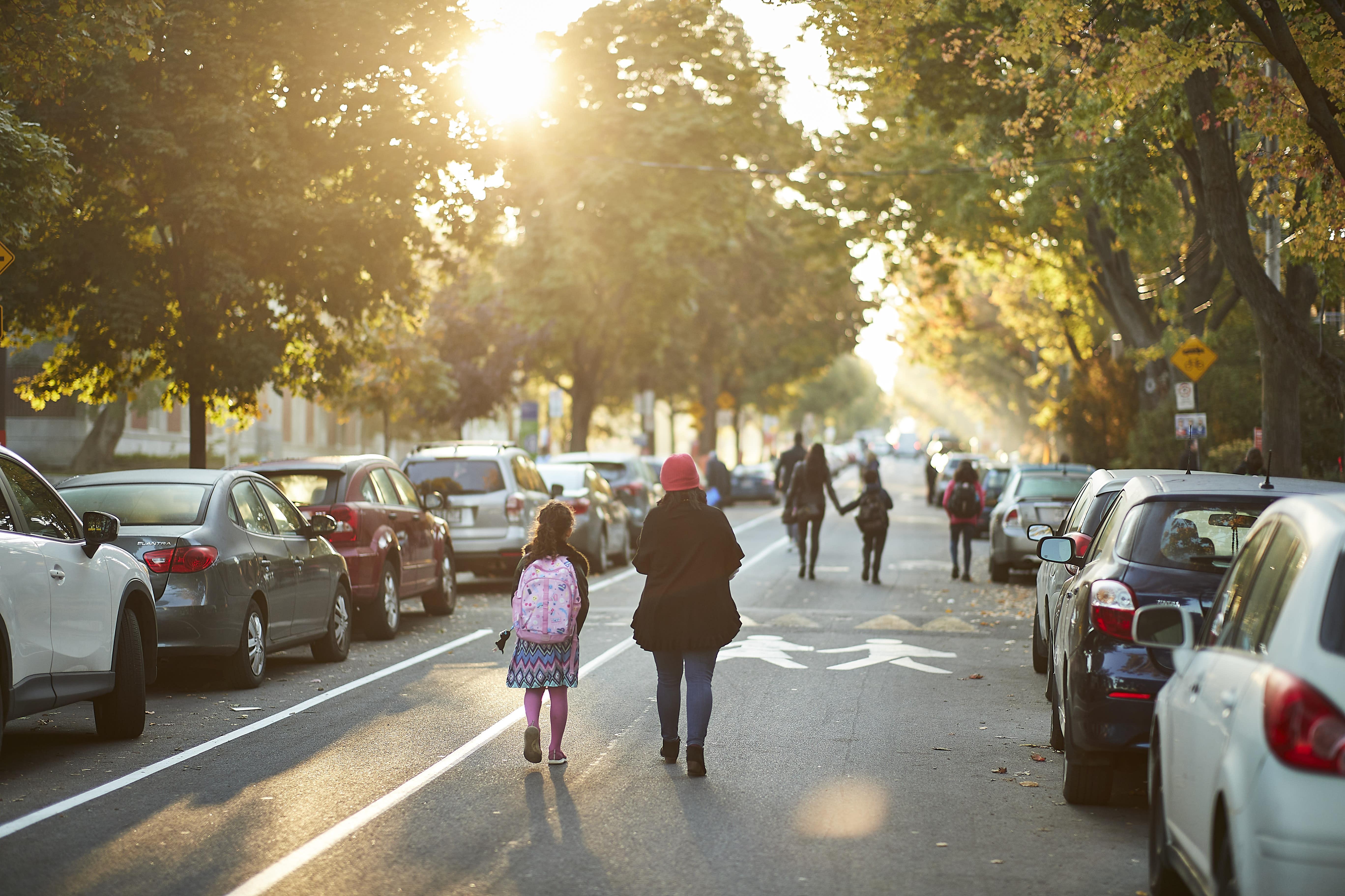 Parents et enfants qui marchent dans la rue-école
