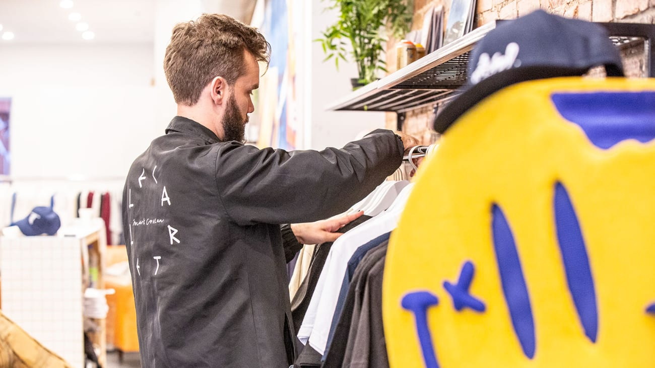 Un employé place des vêtements dans une boutique