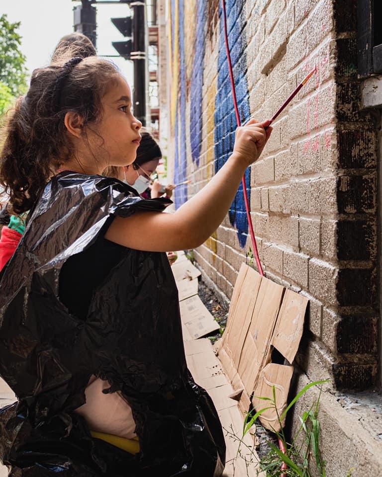 Des enfants peignent le bas d'une murale