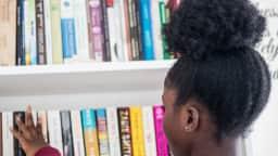 Jeune fille qui choisit un livre dans les rayons d'une bibliothèque.