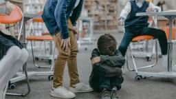 Un jeune garçon assis au sol dans une bibliothèque est entouré d'enfants qui le harcèlent.