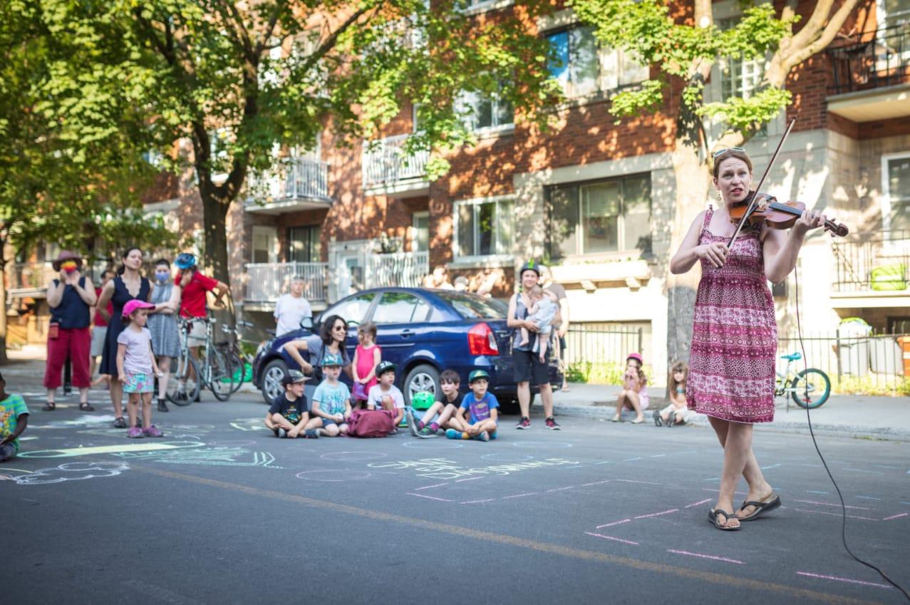 Une violoniste joue sur une rue barrée à la circulation. Des enfants écoutent attentivement.