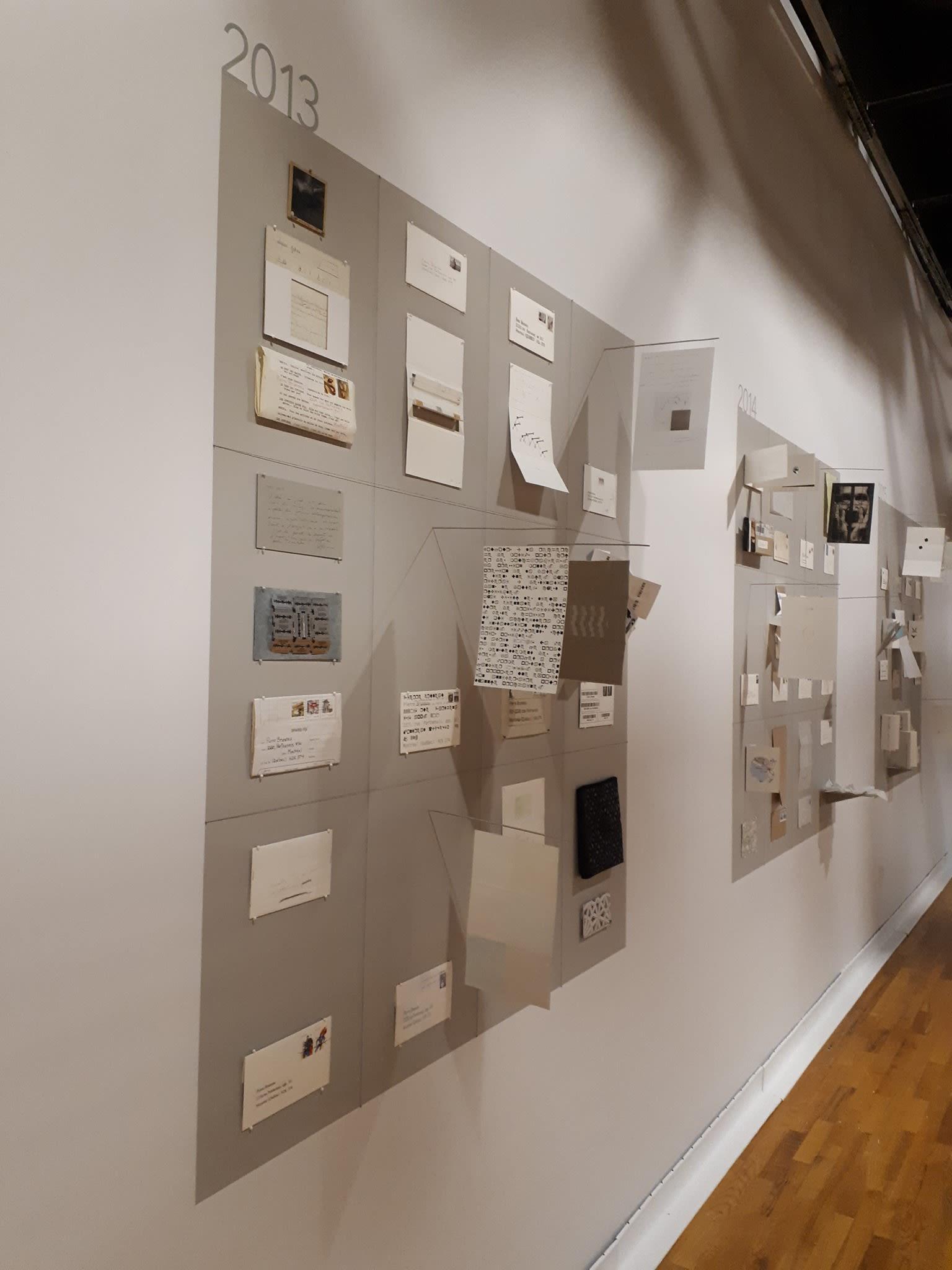 Les oeuvres d'art postal exposées sur un mur blanc