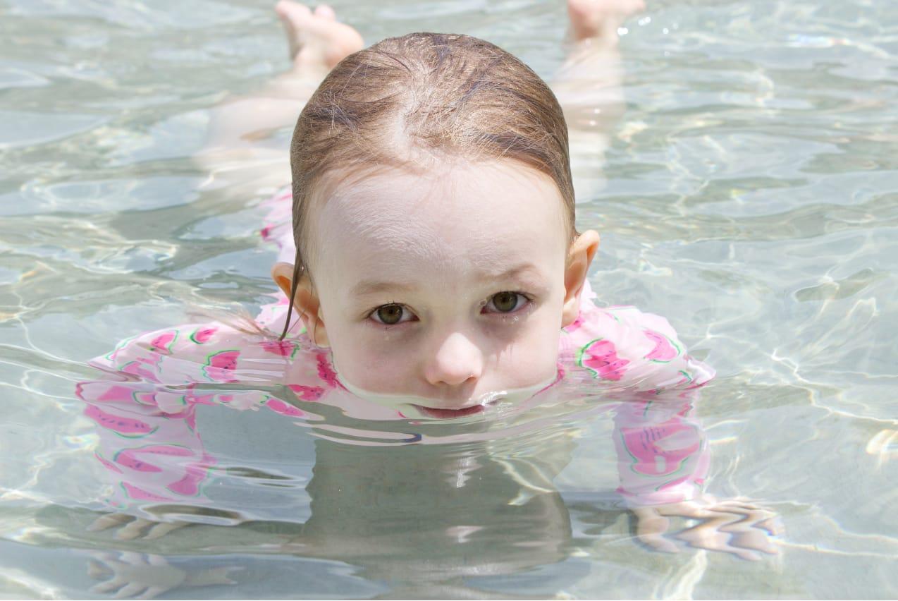 Petite fille dans l'eau d'une pataugeoire