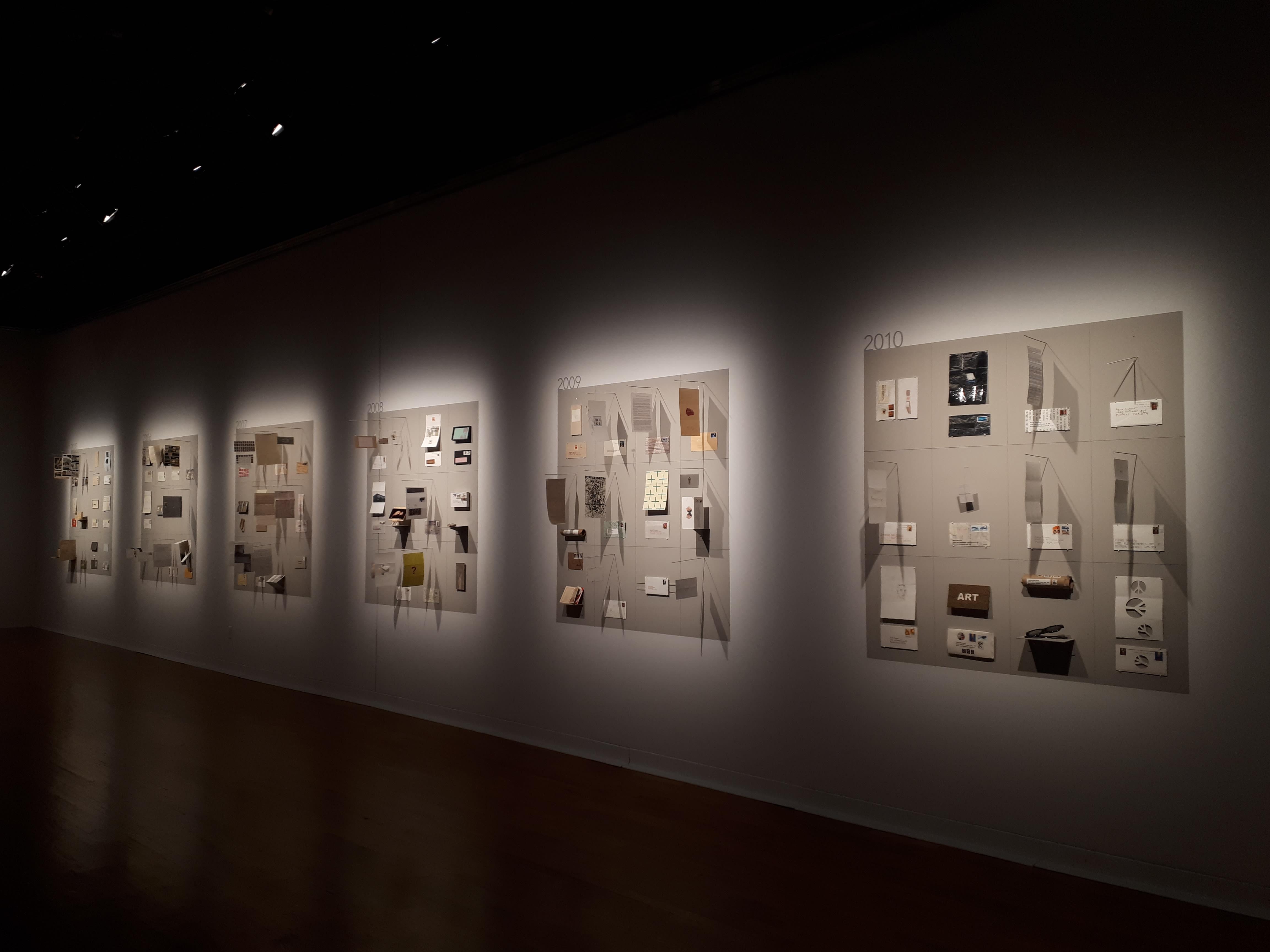 Les oeuvres d'art postal de Pierre Bruneau exposées sur des murs et éclairées par le haut.