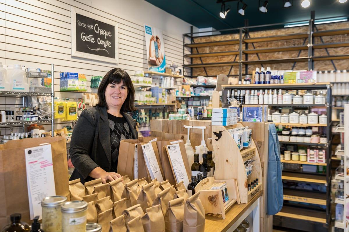 Une commerçante entourée de produits naturels et souriant à la caméra.