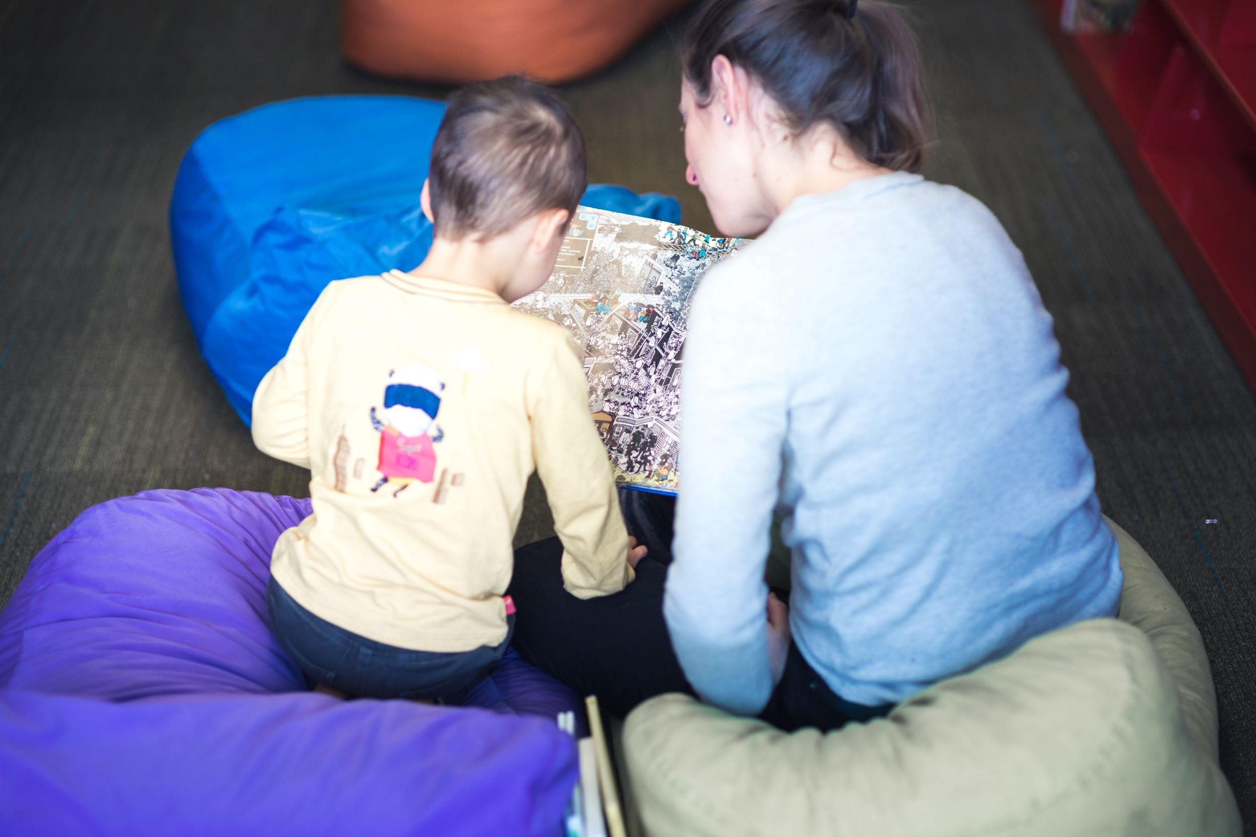 Un enfant et un adulte de dos qui lisent une bande dessinée