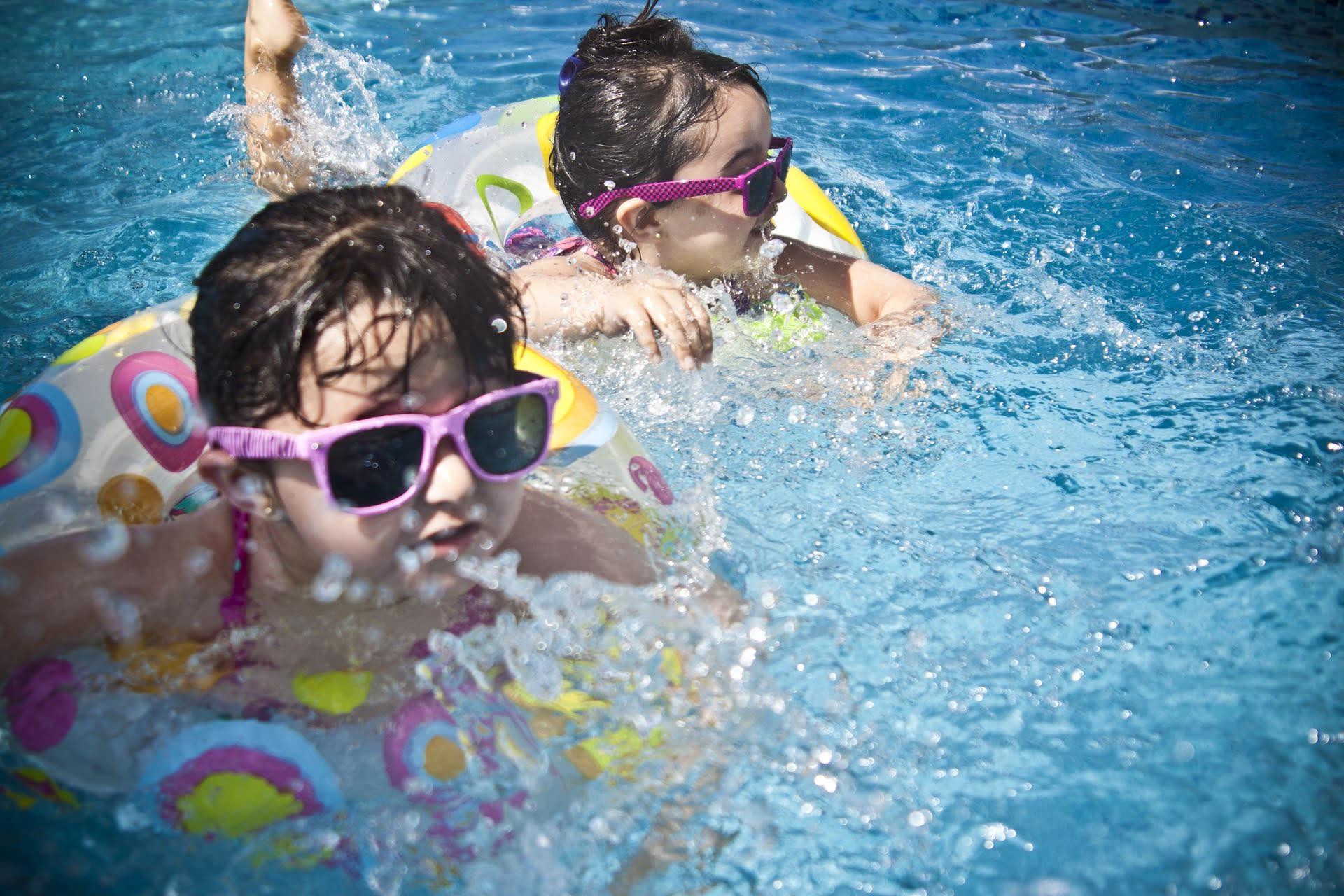 Deux enfants avec flotteurs dans l'eau
