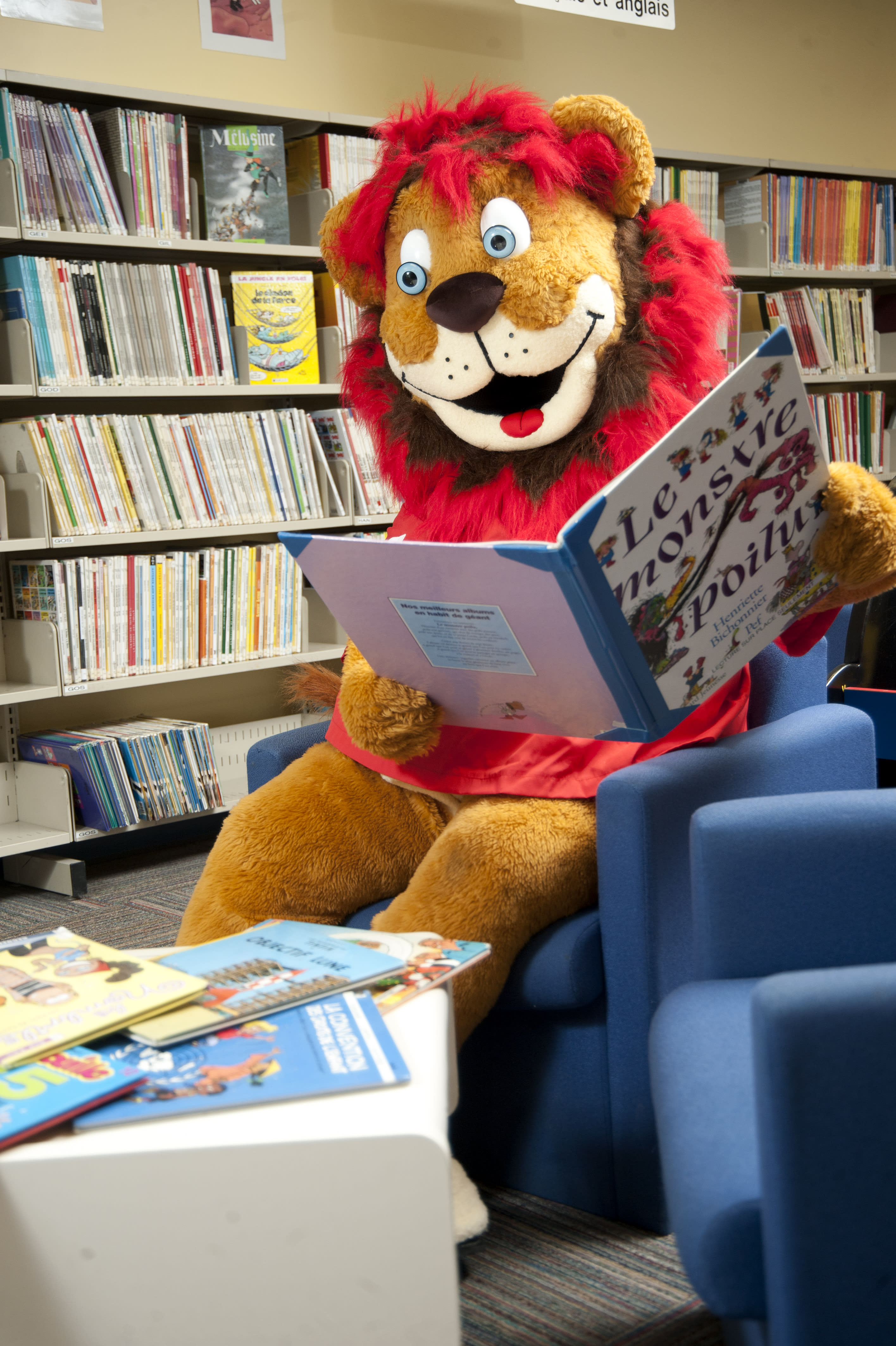 La mascotte Léo qui lit à la bibliothèque