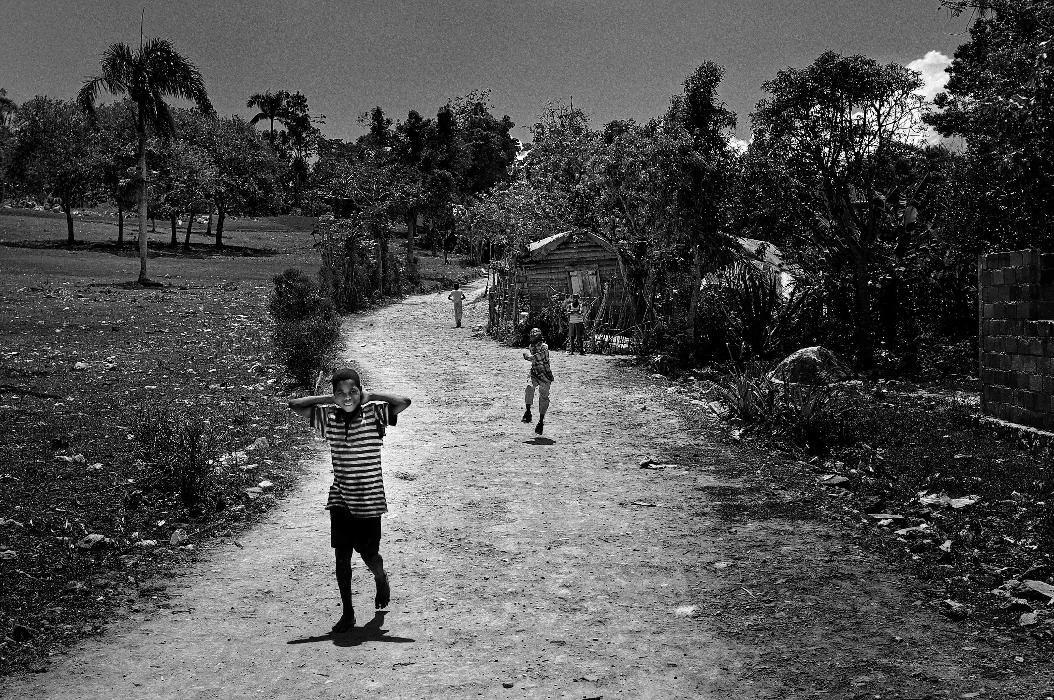 Photo en noir et blanc d'un chemin de campagne avec au premier plan un jeune garçon souriant