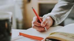 Bras d'une personne qui écrit dans un cahier.