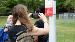 Photo d'une citoyenne qui prend en photo le code QR inscrit sur la signalétique